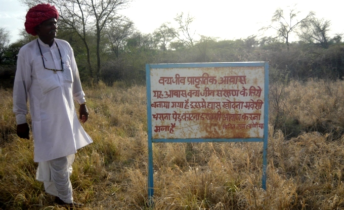 A villager  standing next to a board in Lapodiya that requests people not to pester the wild animals and notifies them of the ban on cutting trees and on any encroachment in the pasture