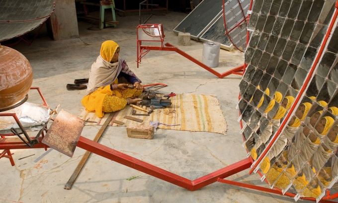 A rural woman-turned solar engineer making a solar cooker to promote cooking with clean fuel  (Image by Knut Erik-Helle)