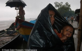 A woman with her child waits for relief in heavy rain. Local people have lost their homes and jobs as a result of the floods. The floods were caused by the change in the course of the waterway on the river Jamuna.