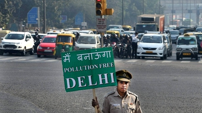 """A cop holding a sign that reads, """"I will make Delhi a pollution free city"""" (Image by Delhi government)"""