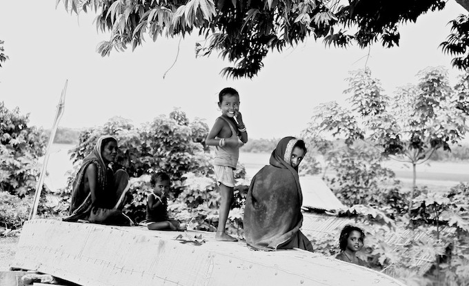 Women of Ramnagar village in Pashchim Champaran district of Bihar sit on an upturned boat during the monsoon and flooding season.