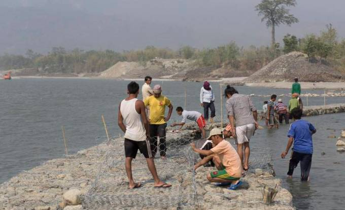 Workers rebuild a vulnerable old wall to protect villages from floods at the Koshi Barrage in Sunsari, Nepal [image by Nabin Baral]
