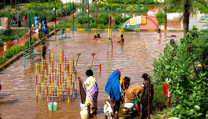 Children using a flooded playground as a swimming pool in Chennai. (Photo by Ben Robinson)