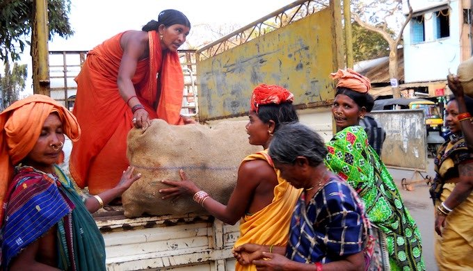 As the sun begins to go down in small town Jaypore in Odisha, tribal women resume their daily wage work of loading sacks of coconuts from a wholesale market. The majority in the global south cannot take days off from work even in extreme heat (Photo by Manipadma Jena)