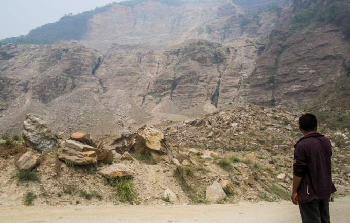 At Sindhupalchowk district in Nepal, a man waits for a bus on the debris of the 2014 Jure landslide on the Bhotekoshi River (Photo by Nabin Baral)
