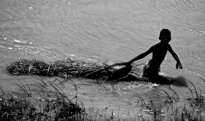A boy drags wet hay through water in Phulparas village in Madhubani district of Bihar. Children play an important role in making the family secure during floods. The numerous challenges they face while doing that usually go unnoticed.