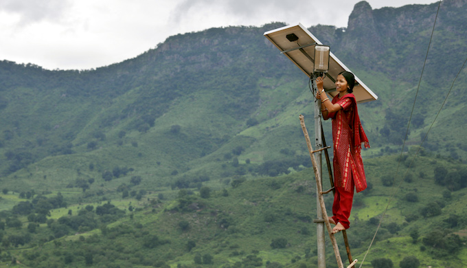A woman carrying out maintenance work on a solar panel. (photo by Abbie Trayler-Smith)