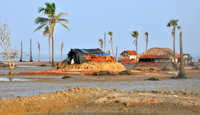 "Dhoblat Sibpur in Sagar Island looks like nature is waging a battle against itself. The area opening up to the sea has few huts barely surviving alongside few trees. ""This is our fourth house. Every time during the high tide, we fear being washed away,"" says Liala Khatoon, tiptoeing carefully in ankle deep low tide water."