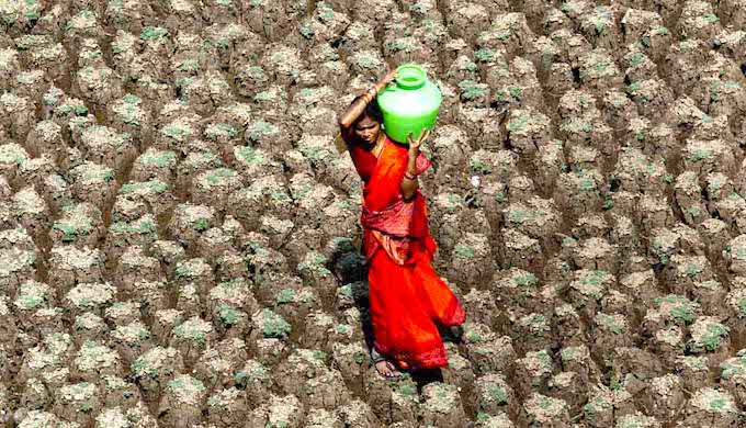 A woman carries home a pot of water while taking a shortcut across the dried up bed of Usmansagar lake in Hyderabad. (Photo by Sherwin Crasto)