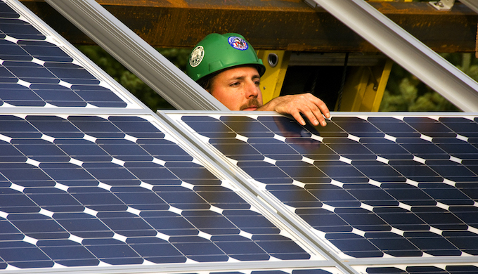 A worker checks the placement of a solar panel.