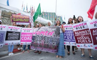 Rise for climate demonstrators in front of the venue of the Bangkok meeting (Photo by Pongsit Nopmaneepaisan)