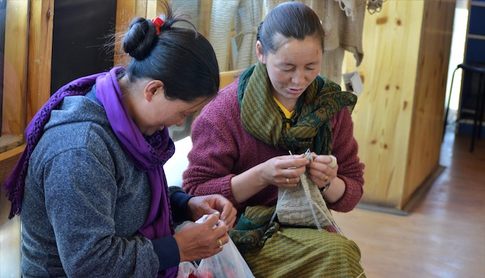 Two nomadic women knitting at a Pashmina shop in Leh owned by a cooperative of nomadic women of Changthang (Photo by Athar Parvaiz)