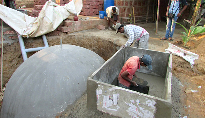 Masons giving finishing touches to a domestic biogas plant in Sindhudurg (Photo by Hiren Kumar Bose)