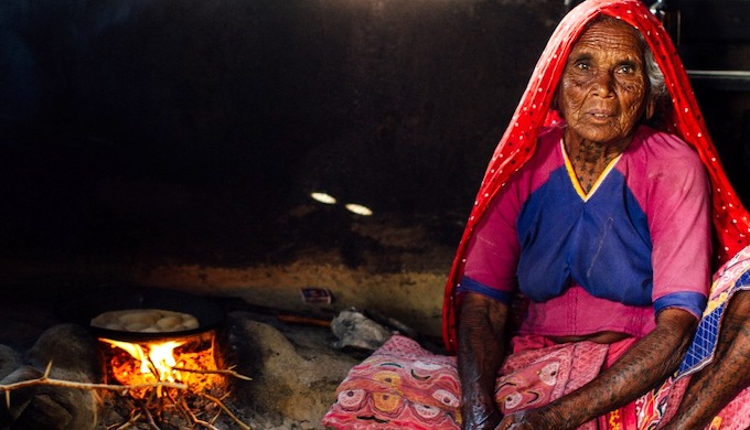 A woman in a village cooking by using traditional biomass fuel (Photo by Adam Cohn)