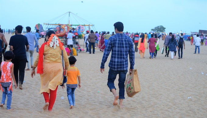 A man carrying stuff in a jute bag as he enters into Chennai's Marina Beach along with his family. Marina beach is one of the most polluted beaches in India.