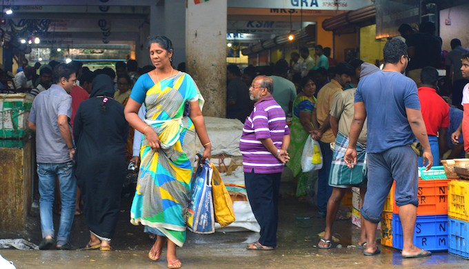 A woman carrying fish she has bought from the market in two non-plastic bags. Since the ban on plastic carry bags came into force on January 1, most people carry their own bags to buy fish