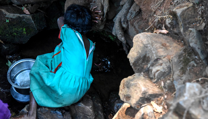 A small girl collecting drinking water from a small stream at Bonda hill (Photo by Tanmoy Bhaduri)