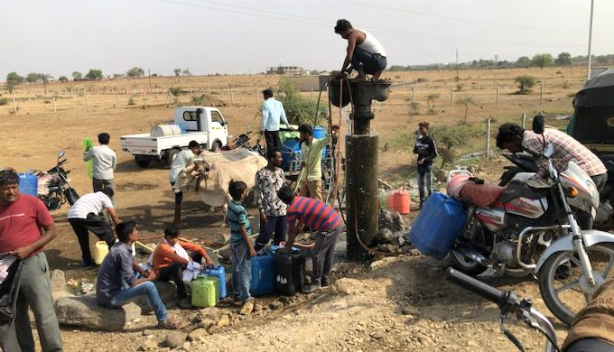 Despite the late morning heat, villagers gather to collect water from a well on the road between Jalna and Beed in Maharashtra (Photo by Joydeep Gupta)