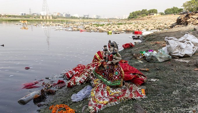 Idols among the garbage and the polluted waters of the Yamuna at Kalindi Kunj in New Delhi (Photo by Richa Singh)