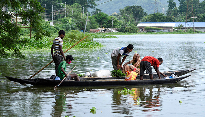 Residents of a village in Assam's Kamrup district escape their flooded village in July 2020 (Photo by David Talukdar/Alamy)