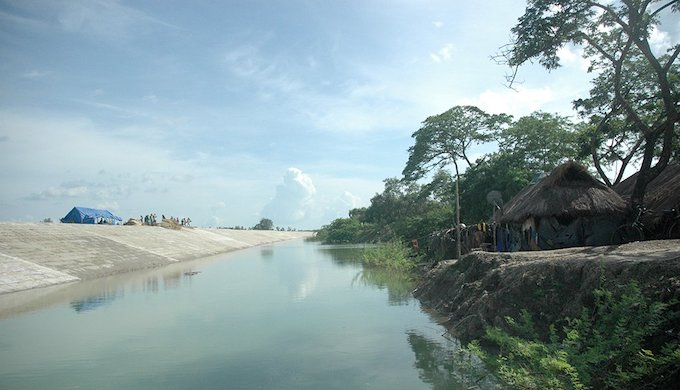 Embankments (left) can displace people, who become more vulnerable as they are forced to rebuild their huts (right) outside the area the embankment protects (Photo by Megnaa Mehtta)