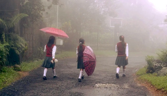 Three young girls walking to school during light rain (slap-boi-ksi), in Mawlynnong village in Meghalaya, one using an umbrella to protect against the rain, one deciding if she should use it or close it, and one walking without an umbrella, almost oblivious to the rain. All of them are enjoying the rain and each other's company. (Photo by Mirza Zulfiqur Rahman)