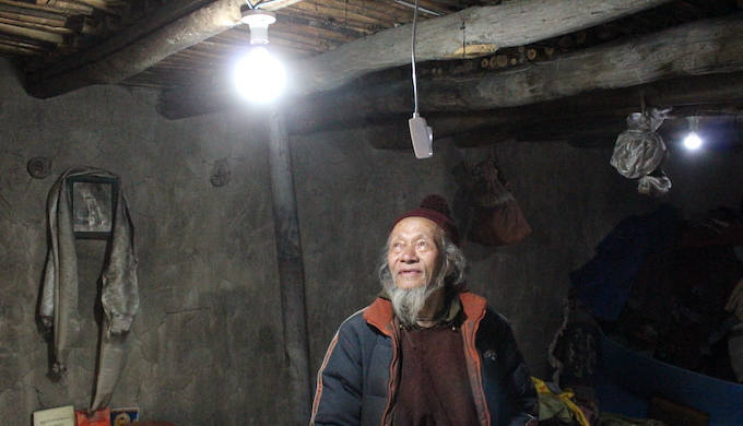 A resident of Machu village in Ladakh smiles after a solar-powered light bulb is switched on for the first time (Photo courtesy: Great Himalayan Expeditions)