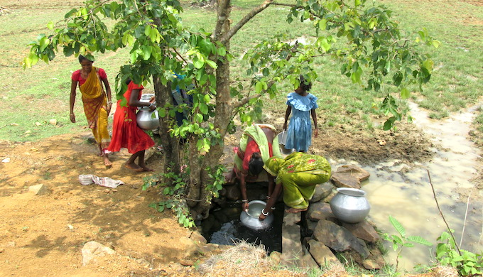 Tribal women fetching water from a shallow well in Odisha province of India (Photo by Abhijit Mohanty)